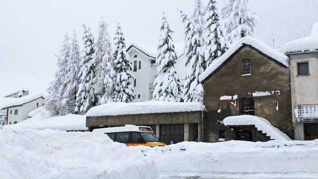 Verschneites Dorf mit einem Postauto