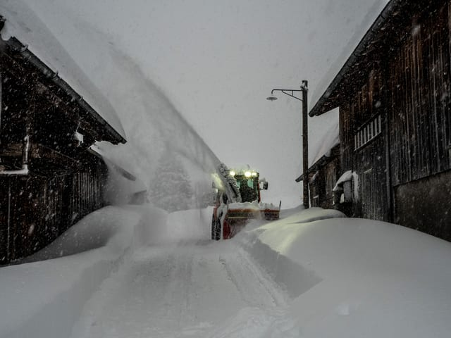Schneeschleider auf Strasse, die meterhoch eingeschneit ist