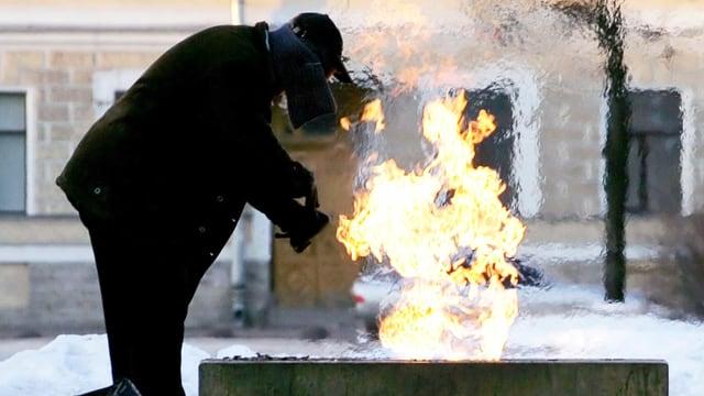Obdachloser wärmt seine Hände über einer grossen Flamme.