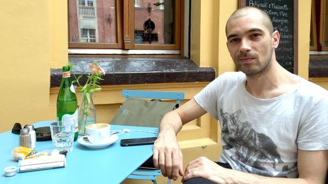 Bafis sitzt in einem Café, vor sich auf dem Tisch ein Handy und eine Tasse Kaffee.