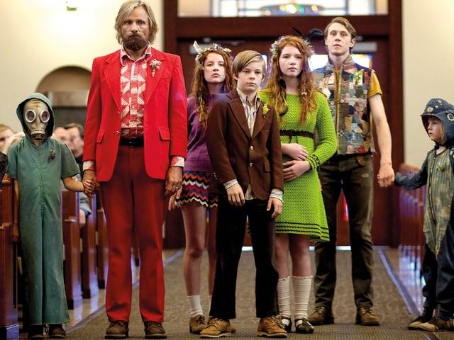 Ein Mann im roten Anzug mit sechs bunt gekleideten Kindern in einer Kirche.
