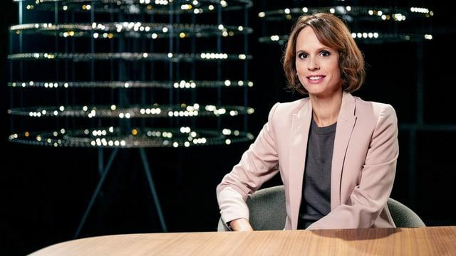 Frau in Blazer sitzt an einem Holztisch vor schwarzem Hintergrund