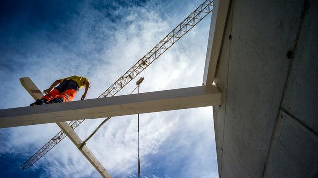 Bauarbeiter auf Stahlgerüst. Bild von unten aufgenommen, der Arbeiter ist also hoch oben und man sieht viel vom blauen Himmel, mit kleinen Wölkchen.