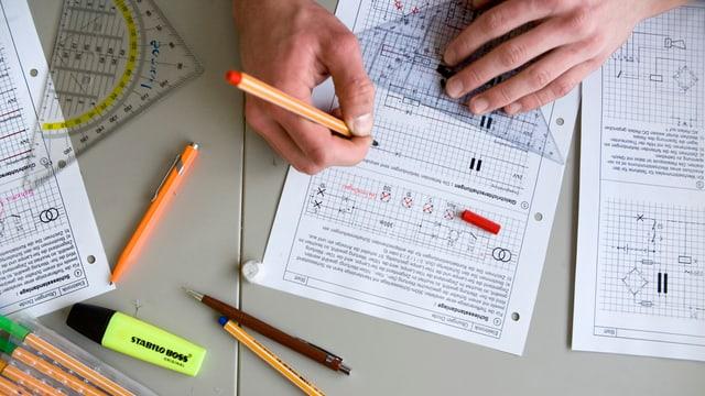 Die Hände eines Schülers. Er arbeitet an einer technischen Zeichnung.
