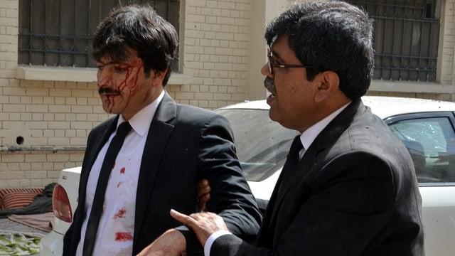 Zwei Männer in Anzügen – einer blutet und wird von einem anderen am Arm geführt.