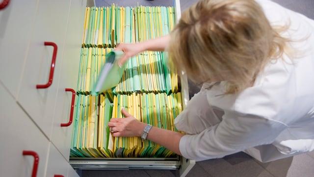 Eine Frau in weissem Kittel räumt ein Dossier in die unterste Schublade eines Aktenschranks.