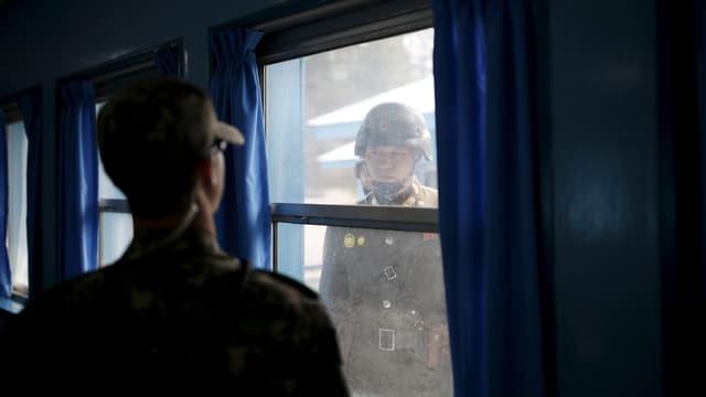 Nordkoreanischer Soldat blickt durch ein Fenster auf einen südkoreanischen Soldaten.