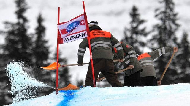 Zwei Zivilschützer in den orangen Jacken schaufeln Schnee aus der Lauberhorn-Piste