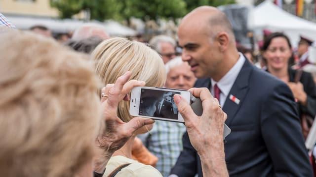 Cusseglier federal Alain Berset entamez la populaziun, ina seniora fa ina fotografia cun ses telefonin.