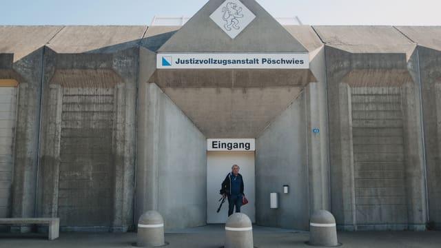 """Betonfassade eines Gebäudes, ein Mann steht vor einer Tür mit grossen Schild """"EinganG""""."""