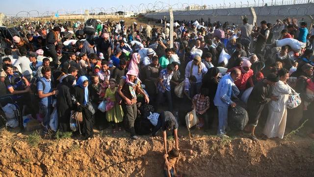 Menschenmenge an einer Mauer mit Stacheldraht