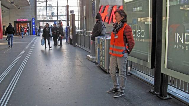 Eine Frau steht in einer Bahnhofhalle mit oranger Leuchtweste und wartet.