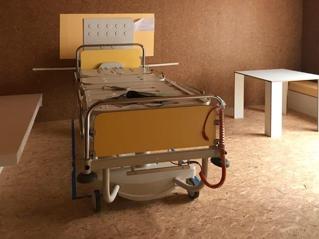 Ein Spitalbett steht in einer Holzbox, an der Wand die Simulation von verschiedenen Anschlüssen.