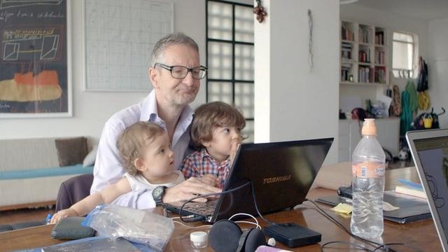 Der zweifache Vater Thomas Haemmerli tippt mit seinen Kids auf dem Schoss etwas in seinen Laptop.