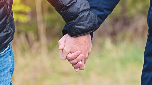 Zwei Männer halten Hände in Jacken.