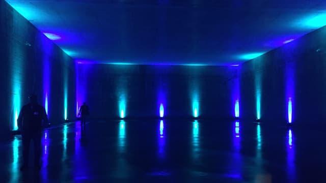 Ein grosser, karger, fensterloser Raum. Entlang den Wänden leuchten blaue Scheinwerfer.