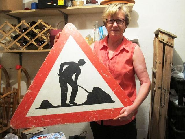 Ursula Diener mit Baustellen-Strassenschild.