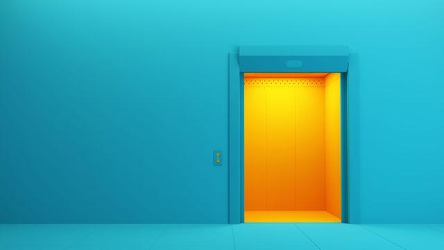 Gelber Liftschacht in blauer Wand.