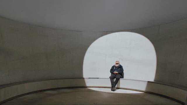 Ein Mann sitzt in einem Gebäude und wird beleuchtet