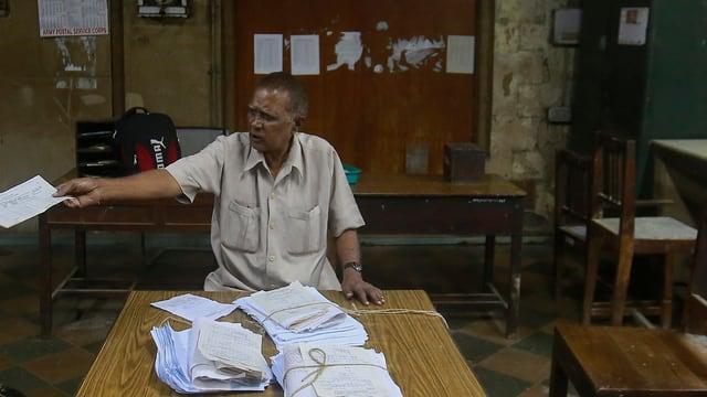 Mann streckt rechten Arm mit einem Papier aus, vor ihm auf dem Tisch liegen Stapel von Papieren