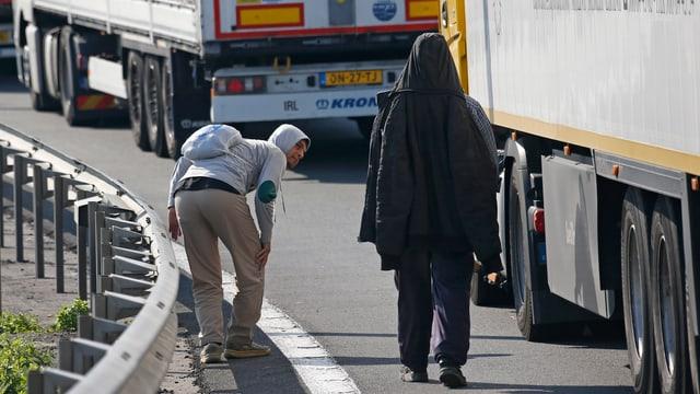 Ein Flüchtling schaut unter einen Lastwagen