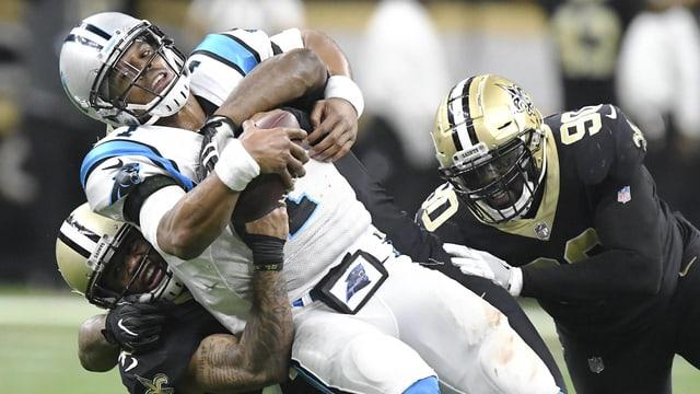 Carolina-Quarterback Cam Newton wird von 2 Gegnern zu Boden gerissen.