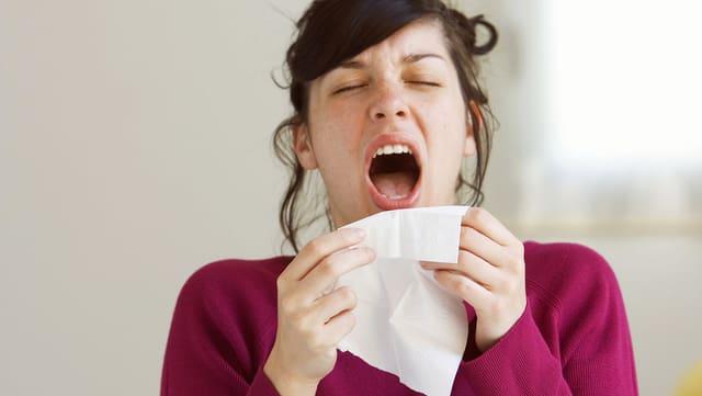 Eine Frau hält die Augen zu und niesst in ein Taschentuch.