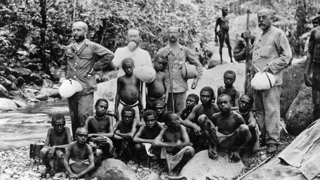 Junge Schwarze mit älteren weissen Männern, die Tropenhelme in der Hand halten.