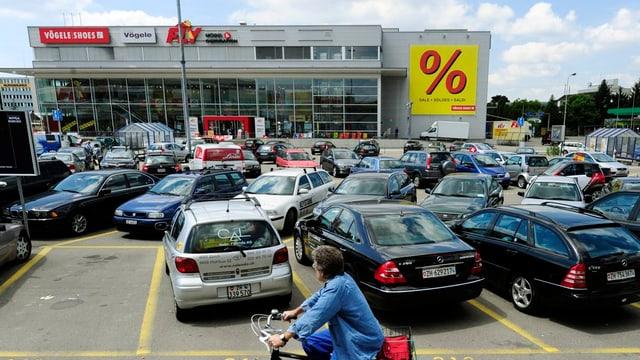 Parkierte Autos vor einem Einkaufszentrum.