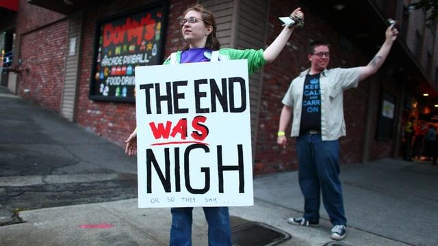 Eine Frau mit einem Schild auf der Brust. Dort steht «The end was nigh» (keystone/archiv)
