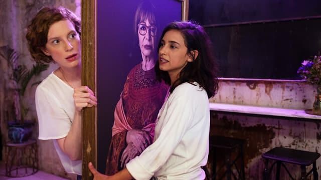 Zwei Frauen tragen ein Bild. Eine grosse rothharige und ein kleine braunharige. Auf dem Bild sieht man eine ältere Frau.