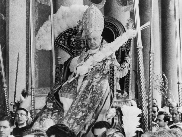 Ein Papst wird in einem Tragsessel getragen. Er ist Teil eines Umzugs.
