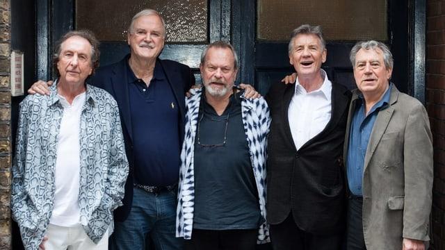 Fünf Männer stehen vor einer grossen Türe.