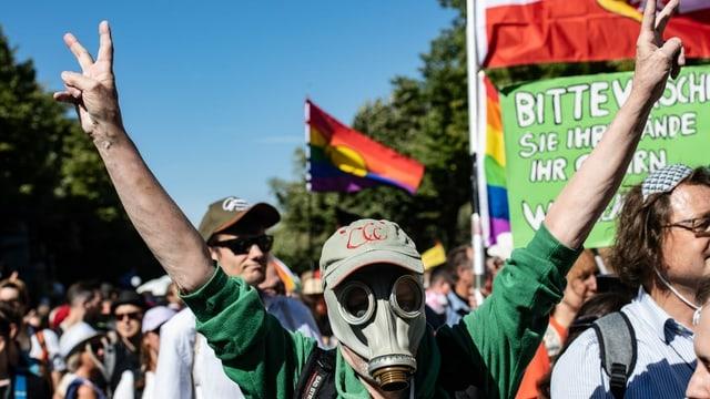 Demonstrationszug. Im Fordergrund eine Person mit Gasmaske und Mütze. Dahinter eine Regenbogenfahne.