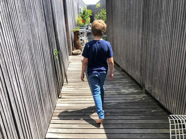 Ein Junge läuft  barfuss auf einem Holzsteg. Der Schatten ist sehr kurz.