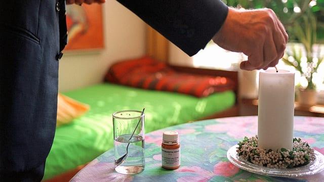 Auf einem Tisch steht das Schlafmittel Natrium-Pentobarbital und ein Glas Wasser. Eine Männerhand zündet eine Kerze an.