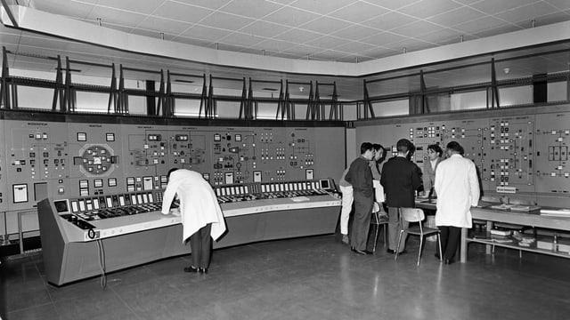 Schwarzweiss-Foto von Männern in Anzügen und weissen Kitteln vor einem Schaltpult