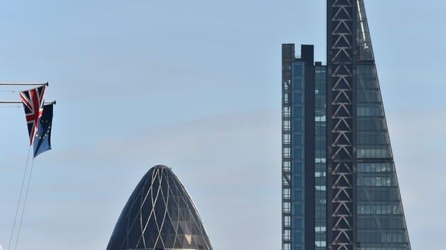 Zwei Wolkenkratzer neben einer EU- und einer Grossbritannien-Flagge.