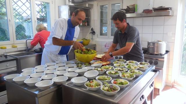 Zwei Männer bereiten Essen in einer Küche zu.