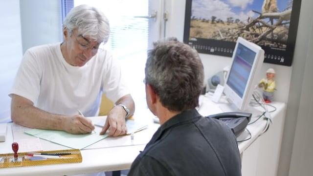 Arzt schreibt, Patient sitzt gegenüber.