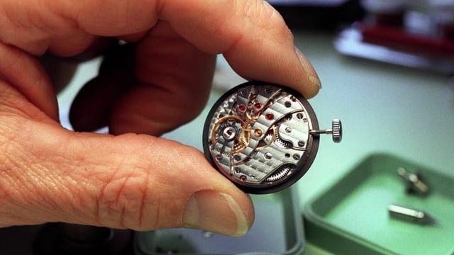 Ein Mann hält ein Uhrwerk.