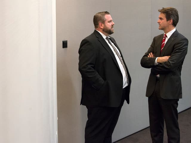 Ein dicker und ein schlanker Mann unterhalten sich.