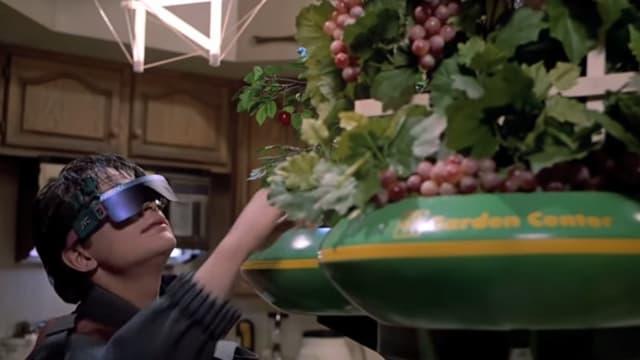 Junger Mann mit dunkler Brille nimmt eine Frucht aus einer futuristischen Früchteschale