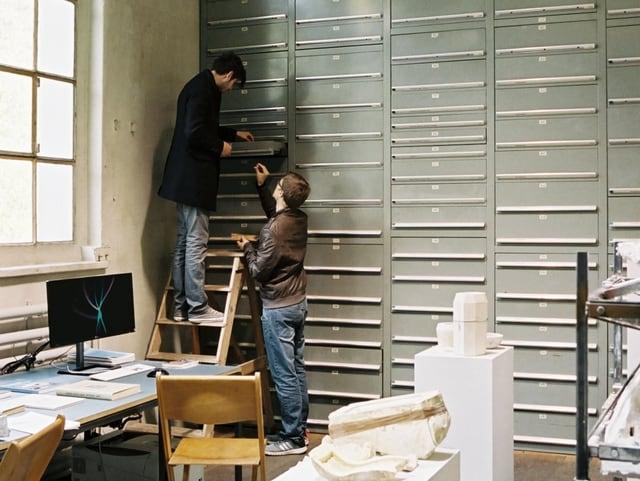 Zwei Männer durchsuchen eine Schublade eines grossen Schubladenregals des St.Galler Werkstoffarchivs.