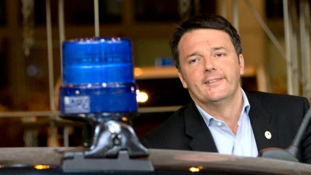 Renzi hinter einem Wagen mit einem Blaulicht auf dem Dach.