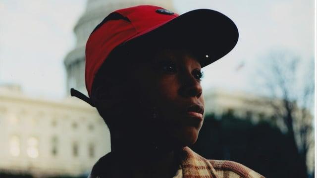 Ein schwarzer Junge mit Mütze schaut in den Himmel