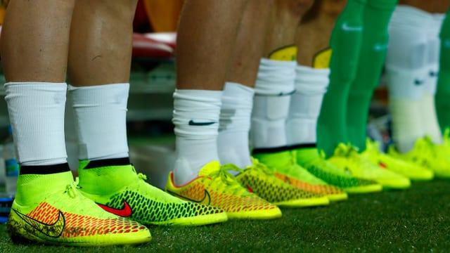 Blick auf die gelben Schuhe von Fussballspielern, die in einer Reihe stehen.
