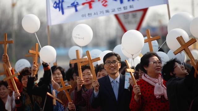 Viele Menschen tragen kleine Holzkreuze und weisse Ballons.