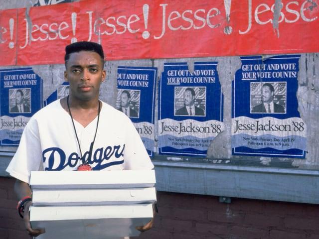 Filmszene: Junger Mann trägt drei Pizzaschachteln
