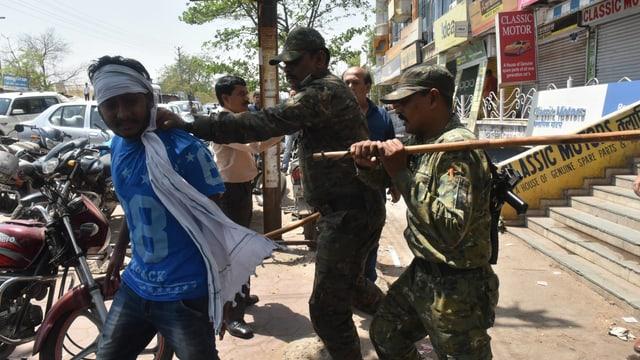 Zwei Soldaten, einer hält einen Mann fest, der andere erhebt einen Holzstock gegen ihn.